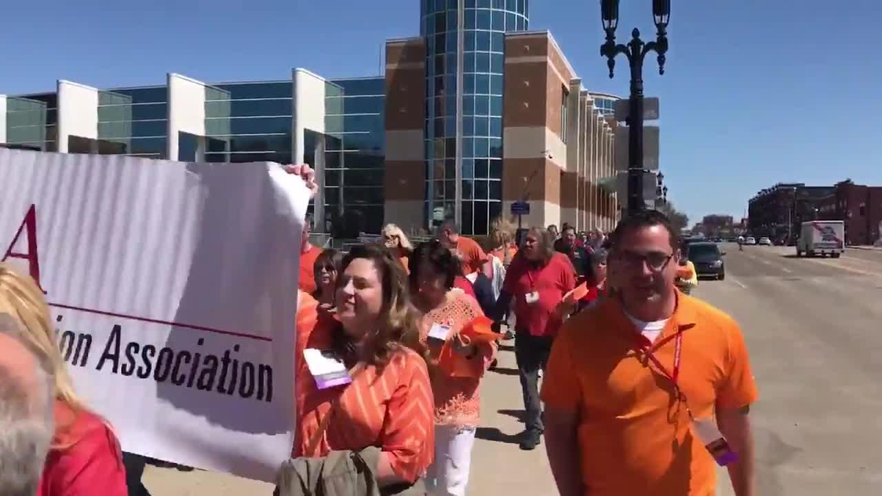 More than 400 Michigan Education Association members marched to the Capitol this afternoon to deliver petitions opposing bills that would allow teachers to have guns in schools.