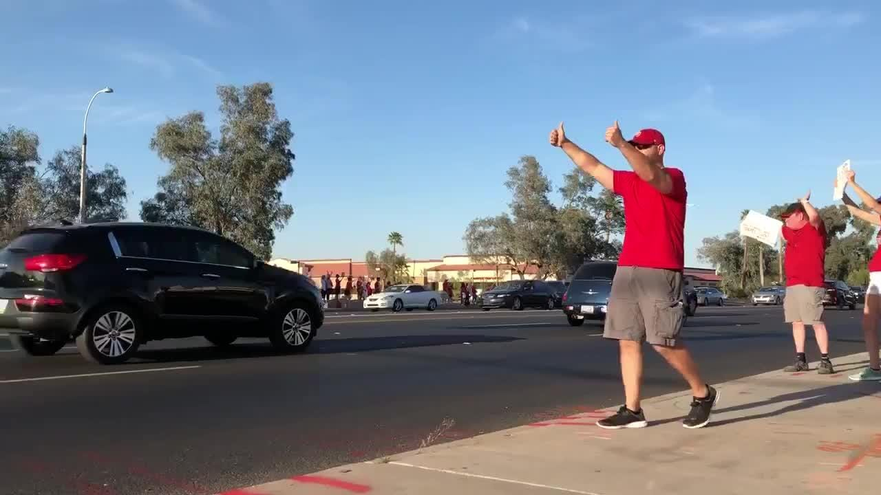 Phil Collins, a middle-school history teacher, engages with cars passing the #RedForEd demonstration along Baseline Road on April 25, 2018.