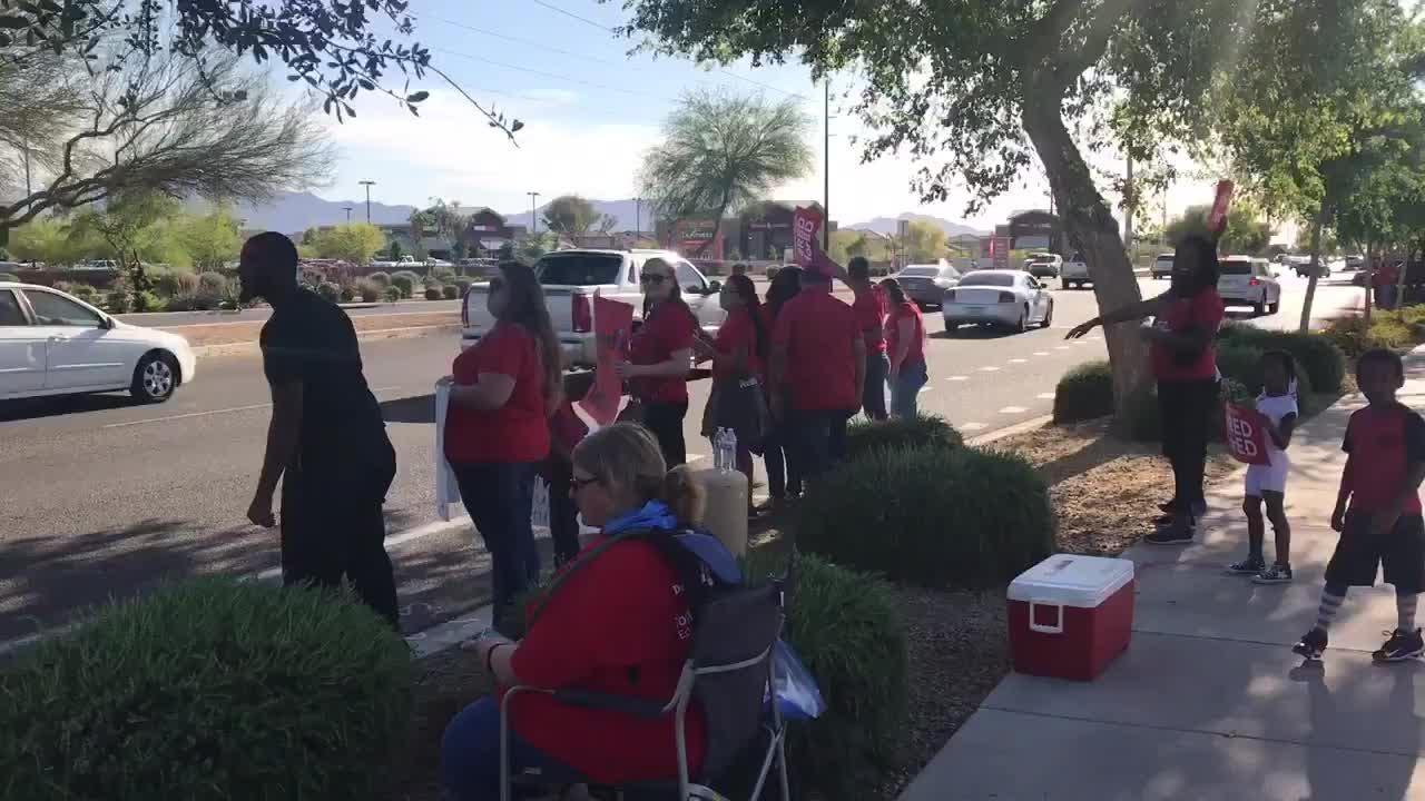 Educadores y simpatizantes de #RedForEd vitorean a los autos en la Avenida 51 y Baseline, en Phoenix