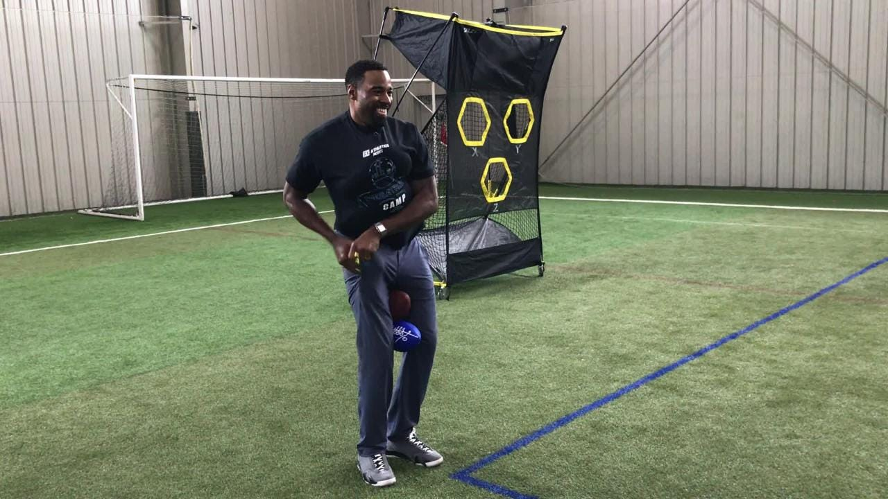 Ex-Detroit Lions star WR Calvin Johnson tries to stuff as many footballs as he can onto his 6-foot-5 frame, at his camp in Pontiac, April 28, 2018.