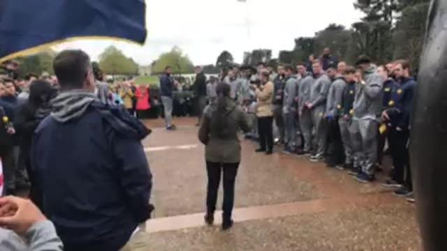 The Michigan football team participates in a ceremony at the Normandy American Cemetery, U.S. soldiers who died during the D-Day landings lie.