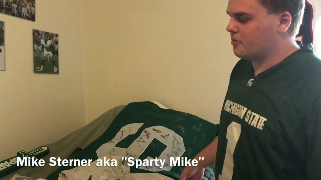 Mike Sterner, aka Sparty Mike, shows some of his favorite Michigan State Spartans jerseys and memorabilia.