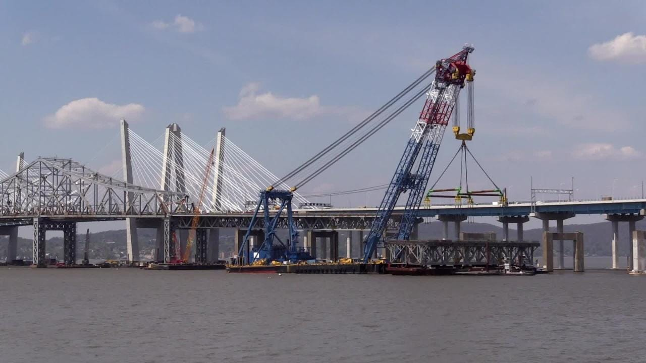 The Left Coast lifter supercrane removes a large section of the Tappan Zee Bridge and a barge carries it away.