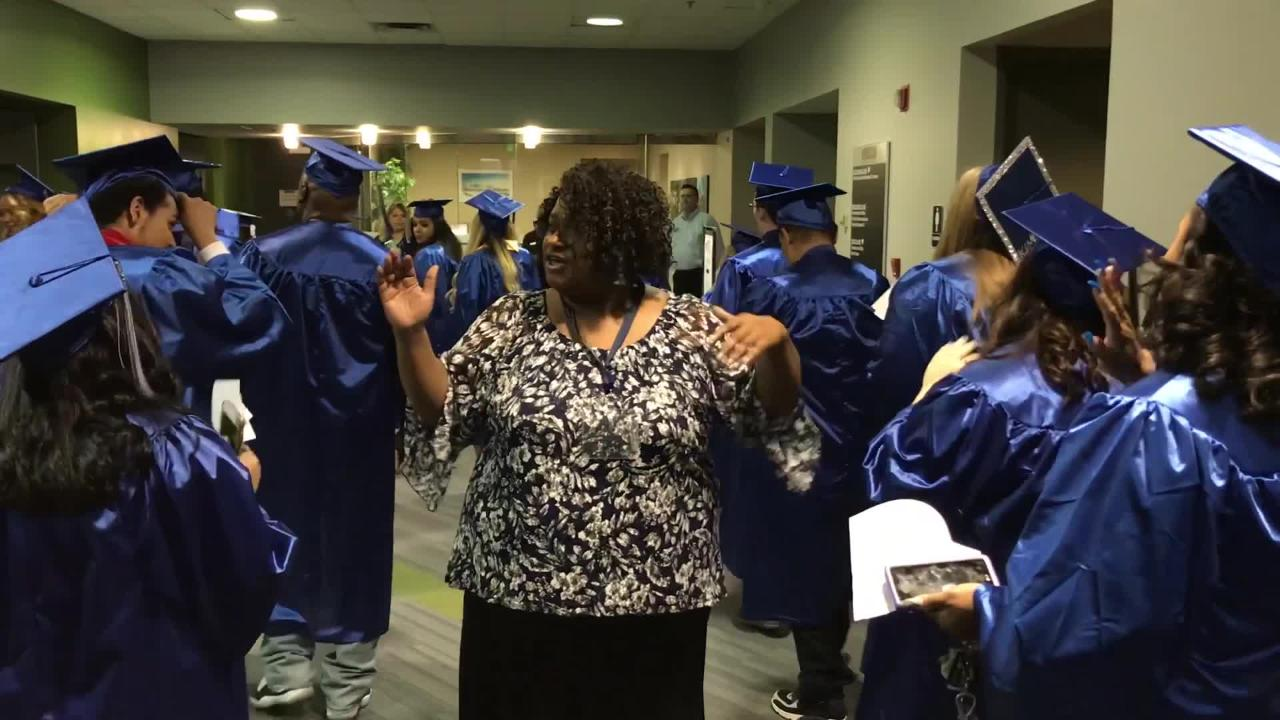 Lansing Community College academic advisor Lisa Alexander high-fives graduates as they make their way to their seats before the commencement ceremony.