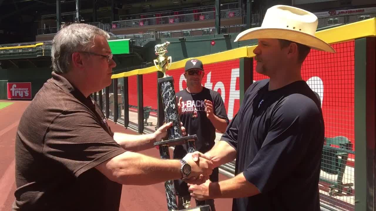 After a stellar performance in which he milked six ounces in one minute, Andrew Chafin accepts the cow milking contest trophy Tuesday at Chase Field.