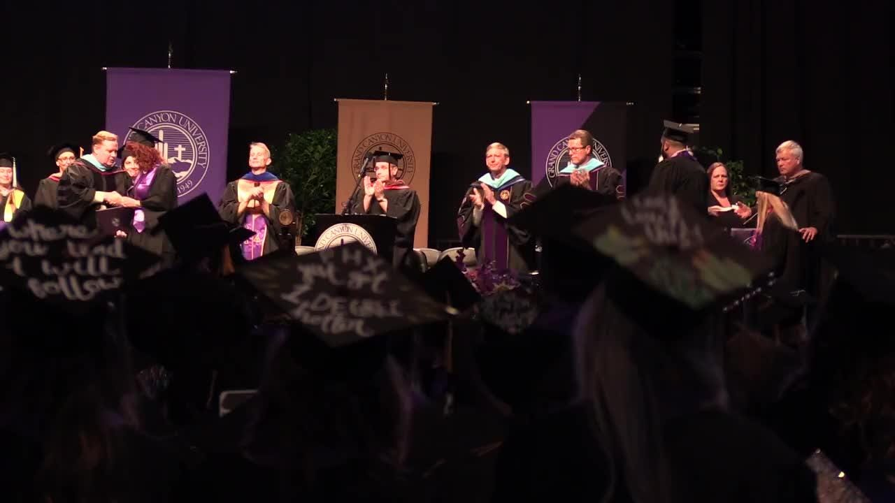 Cathy Hocking accepts a degree from Grand Canyon University on behalf of her daughter, Karli Richardson.