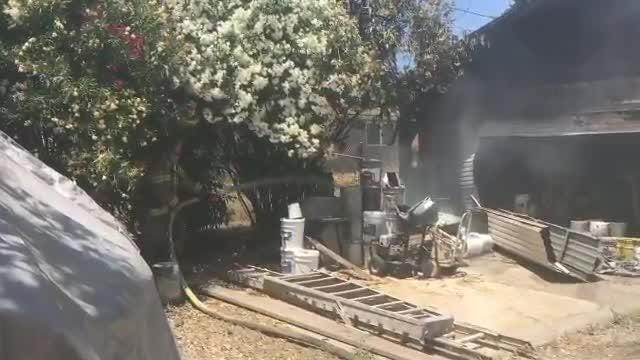 Firefighters mop up after a fire destroyed a garage in Redding