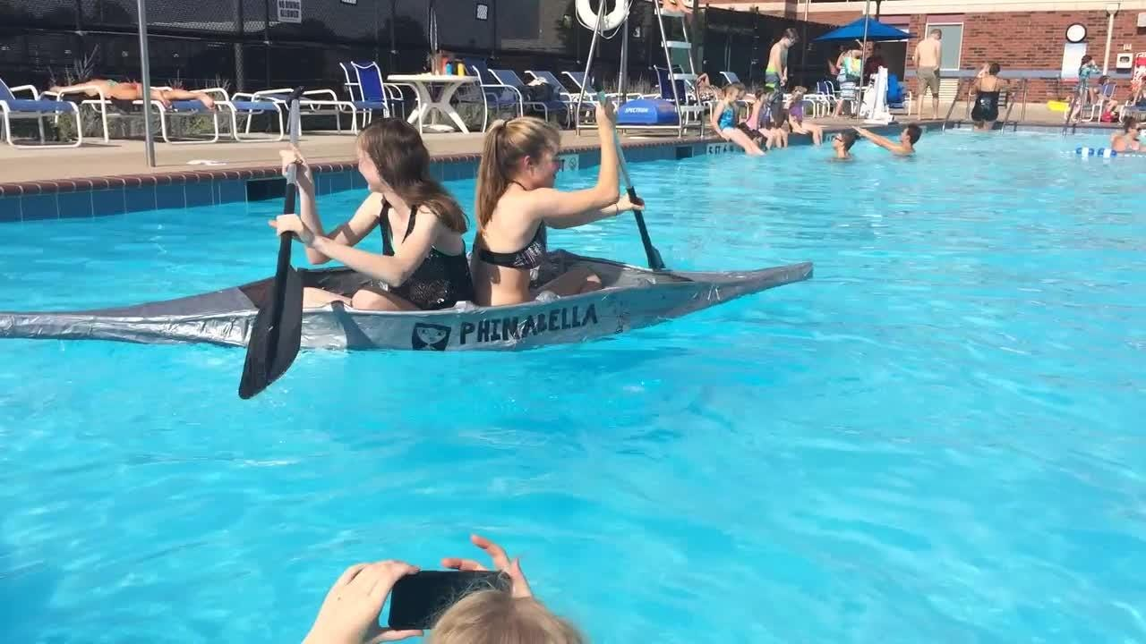 Merrol Hyde Magnet School senior Gracie Gumm and Franklin High School senior Kate Sanborn prove the boat can carry two people. Boat builder Lili Swann of Signal Mountain Middle/High School watches.