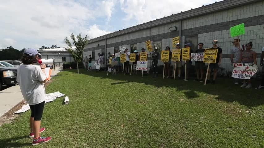 People gather at the ICE detention facility in Crawforville, Fla. for families belong together rally, part of a national movement