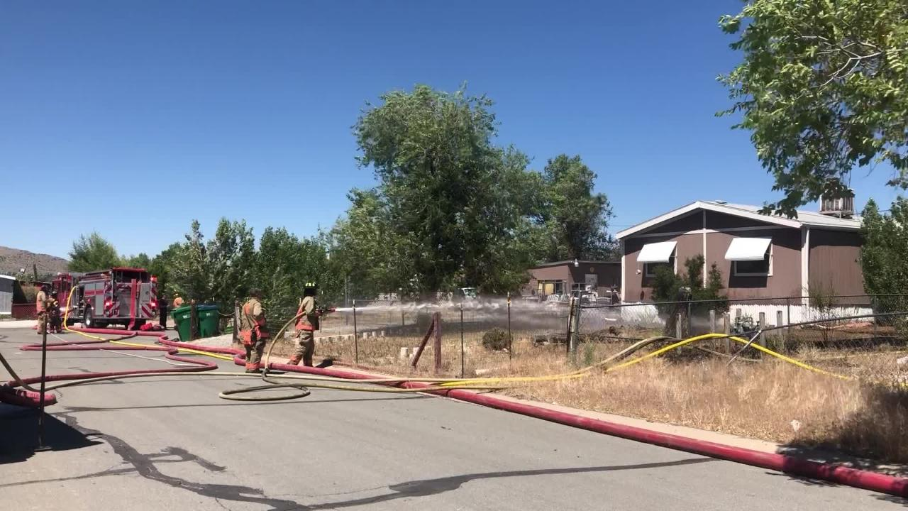 Fire crews work to extinguish a brush fire that spread to damage two homes north of Reno on Thursday July 5, 2018.