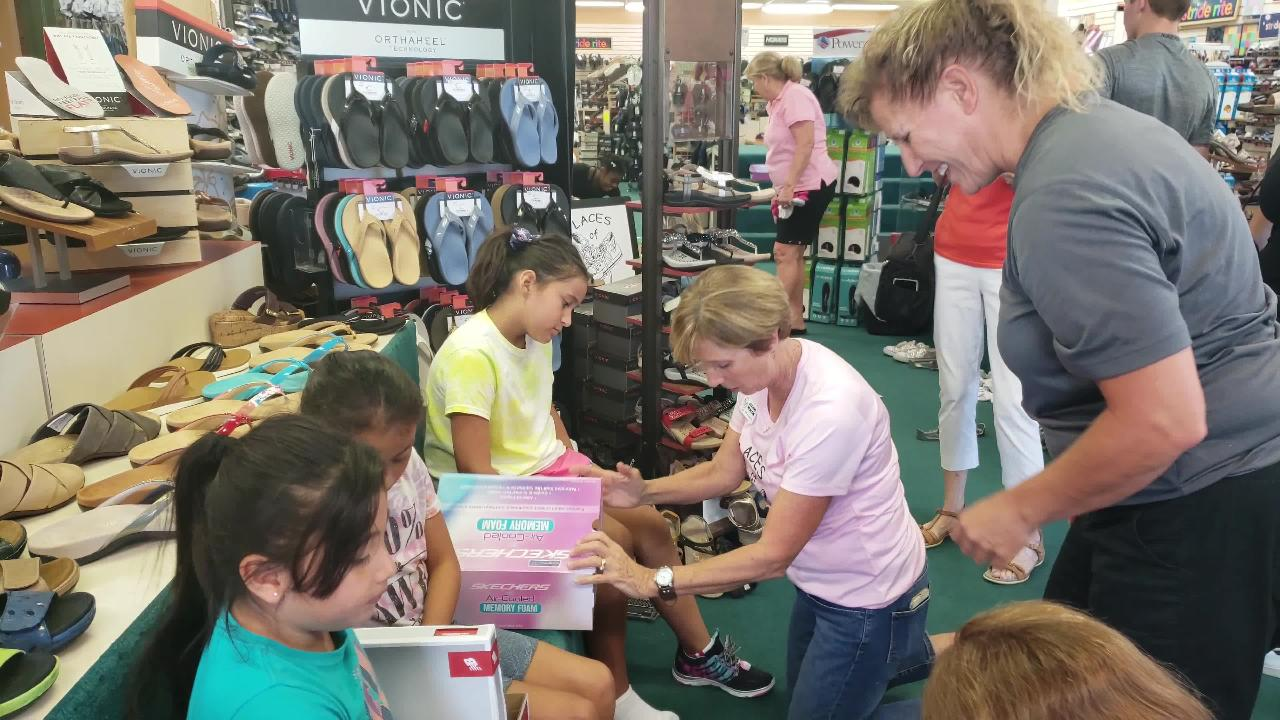 Laces of Love founder Jeanne Nealon helps Jazmine Belleza, 8 of Immokalee, who wears a shoe size 4.5 but came in wearing size 2 shoes.