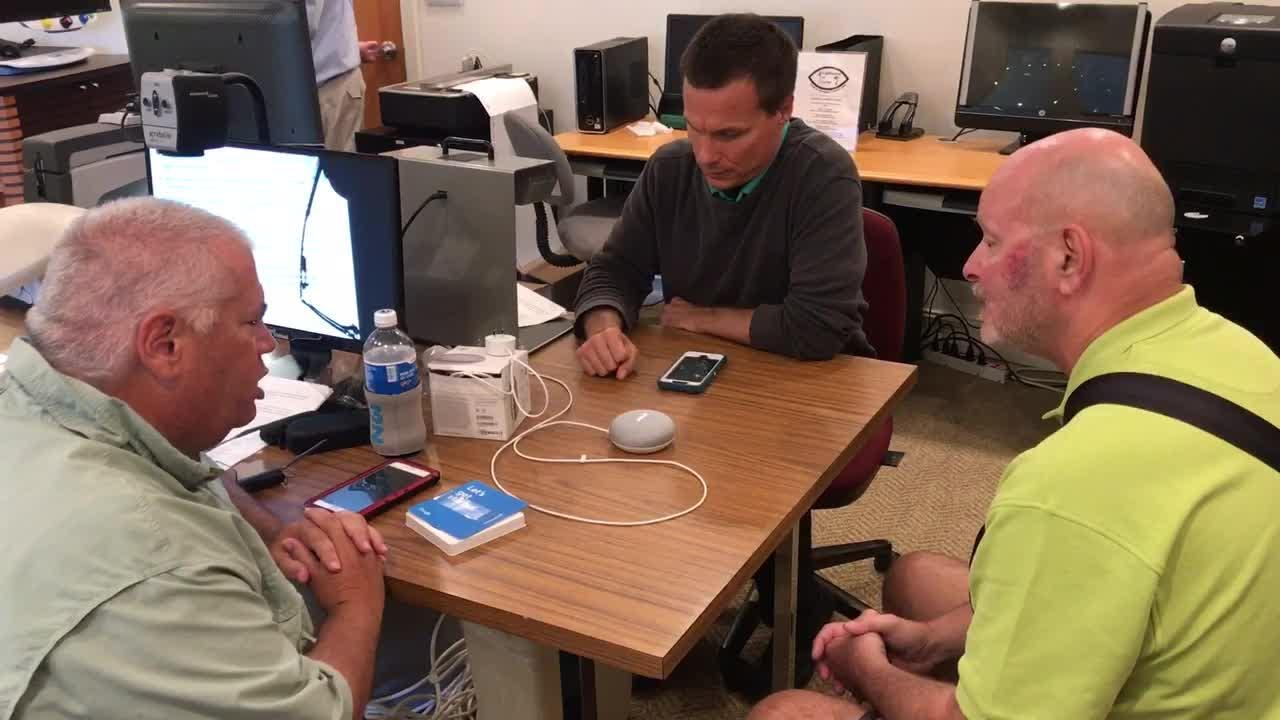 Assistant Technology Instructor Rick Hart, center, instructs how to use the Google Home at Lighthouse of Collier, Inc. in Naples.