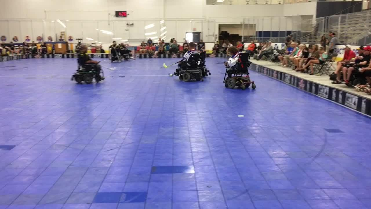 It's fast and can get real crowded in the corners. Wheelchair hockey players battle for the cup.