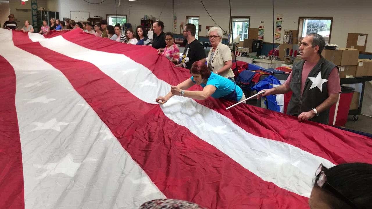 Around 60 Eder Flag Manufacturing Co.  employees in Oak Creek gather around a long work table to help clean and fold a 30-foot by 6-foot American flag recently repaired after it was damaged in Afghanistan.