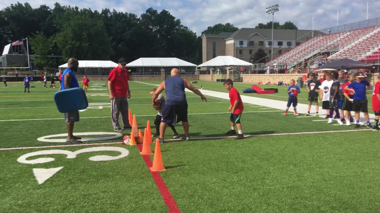 Jim Kelly walks over and helps coach up kids during a tailback drill.