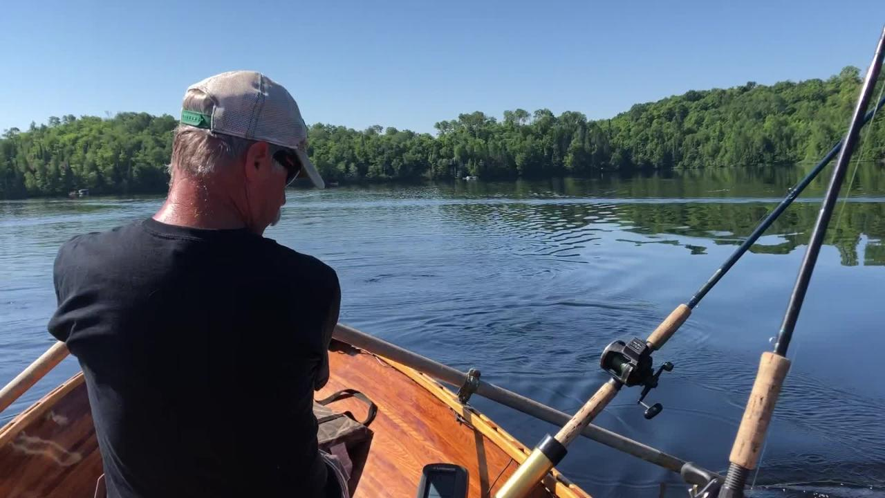 Scott Hassett rows Patrick Durkin's cedar-strip rowboat on Crab Lake as they troll for muskies.