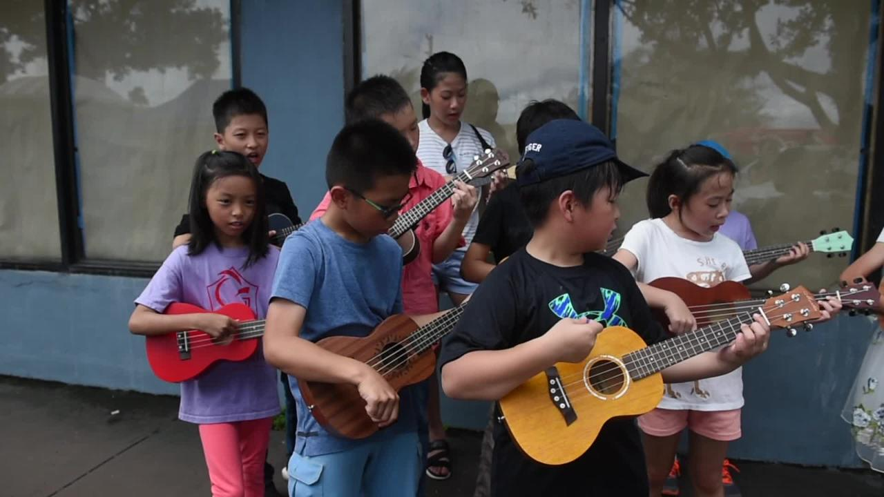 Alexander Tutorial Center students give an ukelele street performance during the 74th Liberation Day Parade, July 21, 2018.