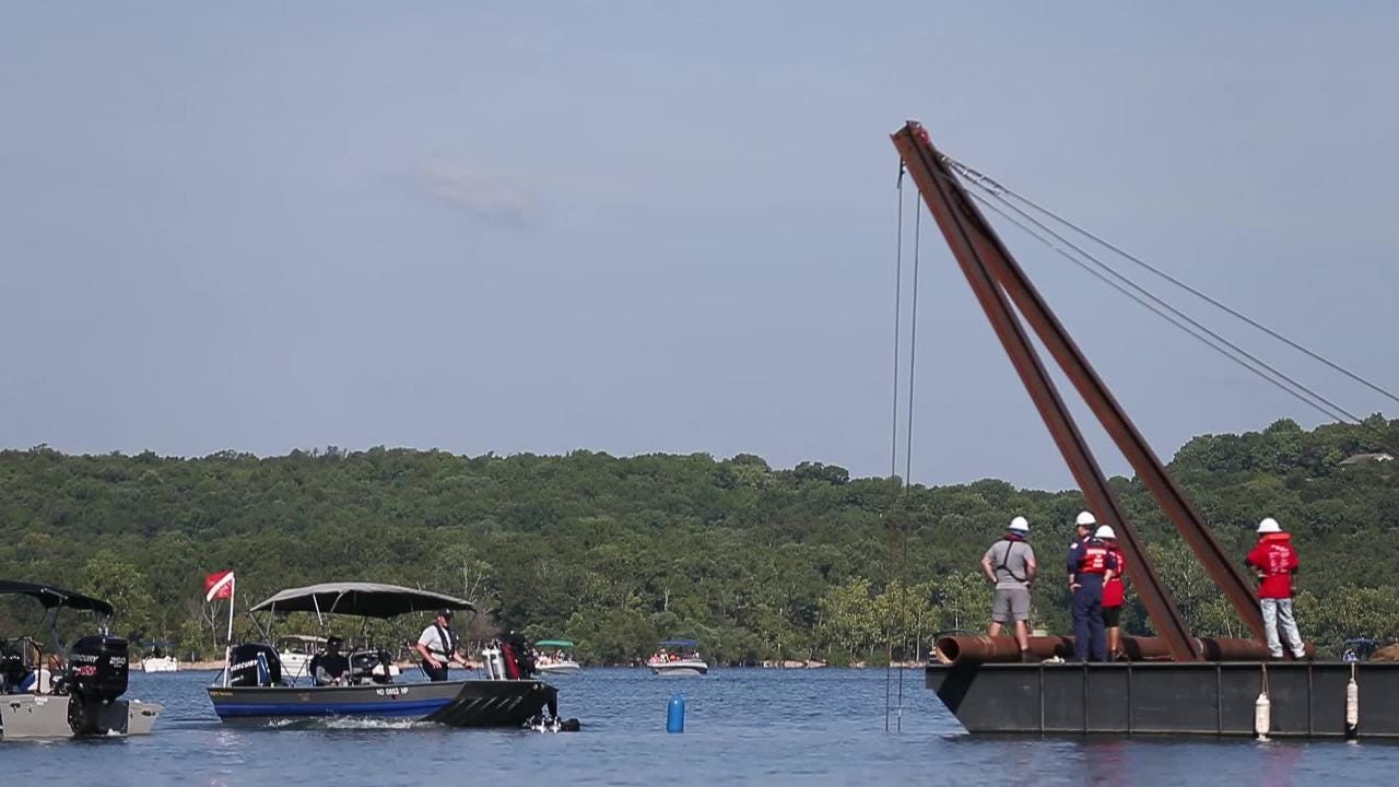 Crews begin the process of salvaging a duck boat from the bottom of Table Rock Lake