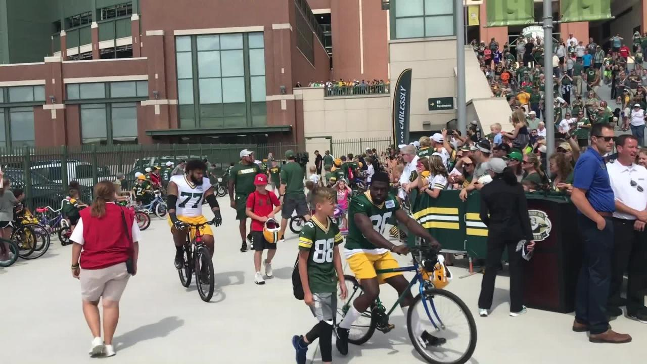 The Green Bay Packers kicked off the first day of training camp by riding young fan's bicycles from Lambeau Field to Ray Nitschke field.