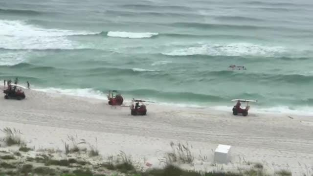 A woman filmed Navarre Beach Lifeguards saving swimmers from a rip current.