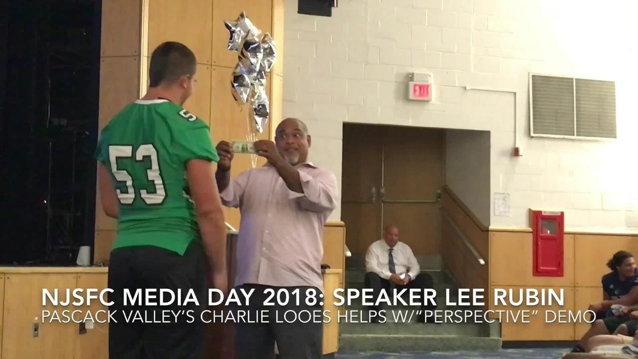 Former Penn State football player Lee Rubin enlists the help of Pascack Valley's Charlie Looes for a demonstration on perspective at NJSFC Media Day.