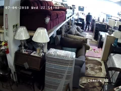 Surveillance video shows a suspect rob the owner of an east-side furniture store at gunpoint