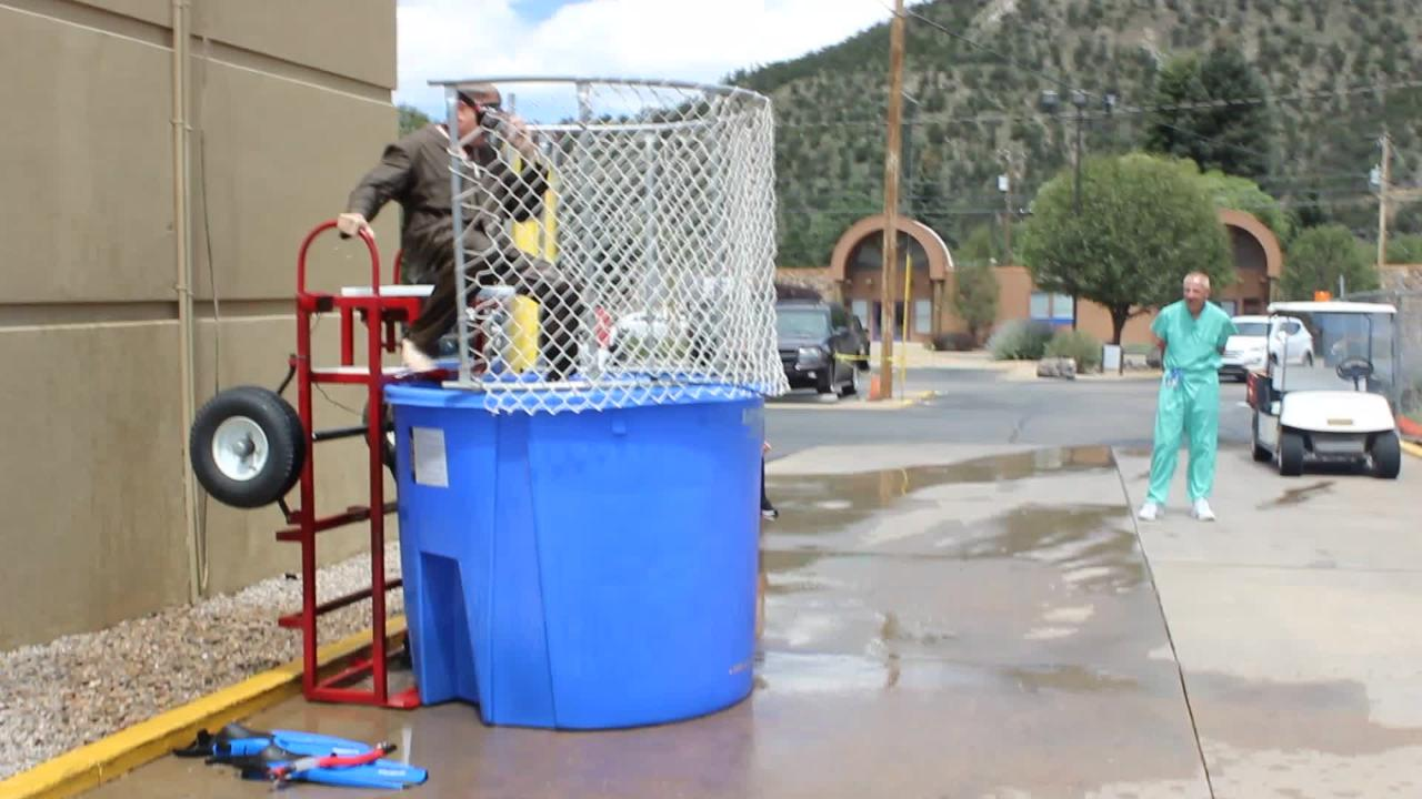 Dr. Otero fires up his guns to dunk Hospital Chief Executive Todd Oberheu into the water below during employee appreciation day.