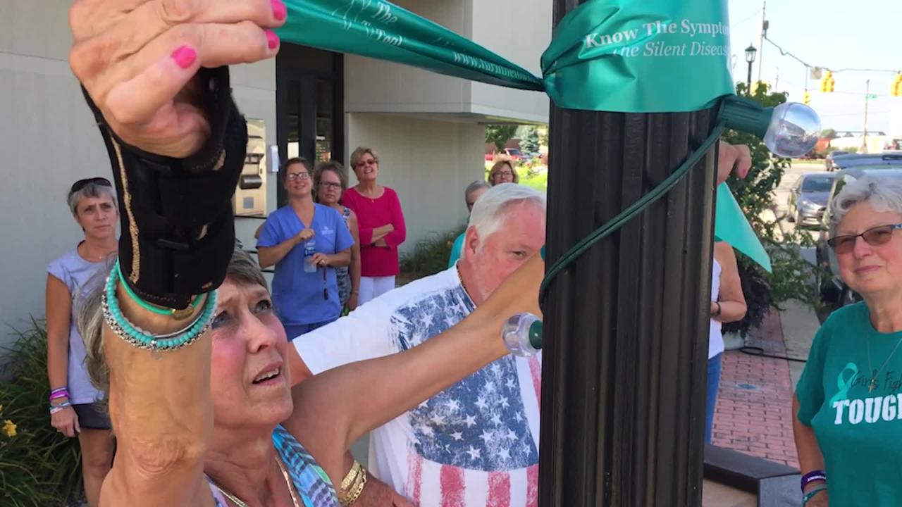 "Patti Tucker of Fremont, part of Ovarian Cancer Connection, hangs teal ribbons downtown to ""Turn the Towns Teal"" for ovarian cancer awareness."