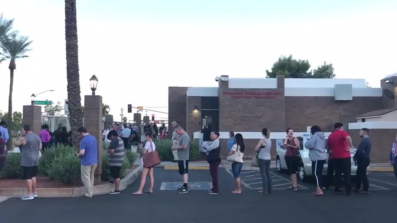 Docenas de votantes hacen fila afuera de la Biblioteca Pública de Phoenix a minutos de que la casilla cierre.