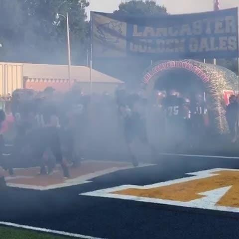 The Lancaster football team takes the field. It was the first game on the new turf at Fulton Field.