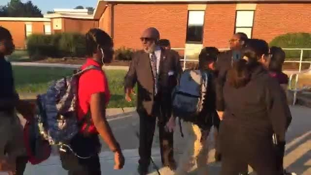 Black men dressed in suits greet students at McKean High School to show them what success looks like.
