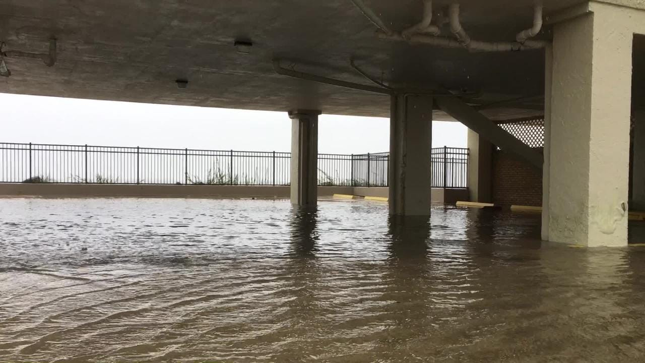As rain and wind continue to pelt North Myrtle Beach, S.C., a parking structure under high rise along the beach floods Friday, Sept. 14, 2018.