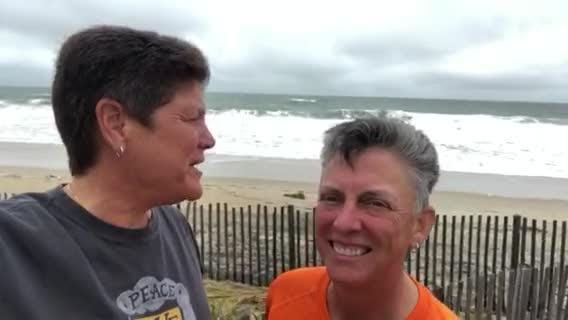 A couple of former central Pa. residents check in with the high tide status at Rehoboth Beach, Delaware.
