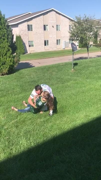 """Alyssa Gruender, a 2016 graduate of Appleton North, acts out a silly skit where she plays a quarterback gently """"sacked"""" by her boyfriend, Sean McGann."""