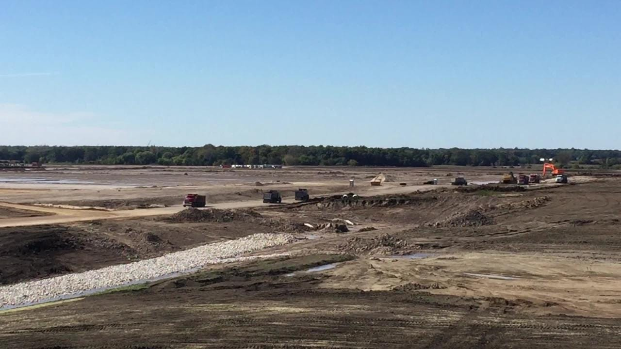 Viewed from atop a 30-foot-high mound of topsoil scraped from the Foxconn factory site, the construction of the massive complex stretches over hundreds of acres where the foundation is being prepared for an initial group of display-panel manufacturing buildings.