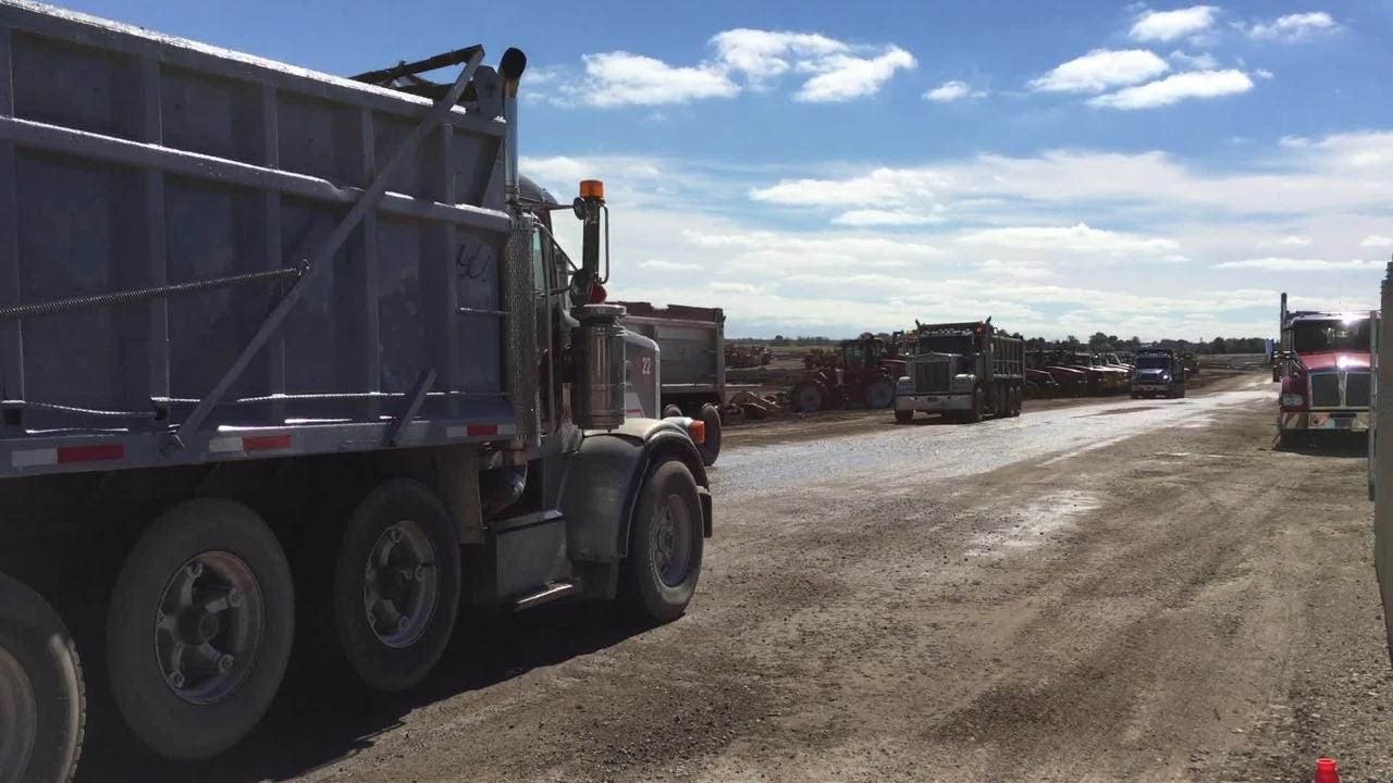 Dump trucks hauling aggregate from four area quarries stream in and out of the Foxconn construction site. Early Thursday afternoon, a dump truck was entering or leaving every 12 seconds.
