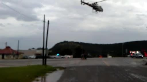 Amid flooding in Junction, Texas, on Oct. 10, 2018, a helicopter lifts a person away from a flooded area.