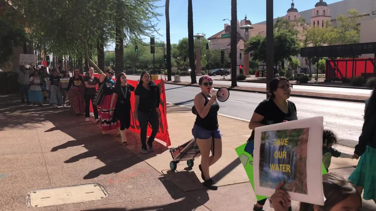 """The Indigenous Peoples March moves along Van Buren Street on Oct. 8, 2018. Some protesters are holding a large sign that read """"Indigenous Peoples Day."""""""