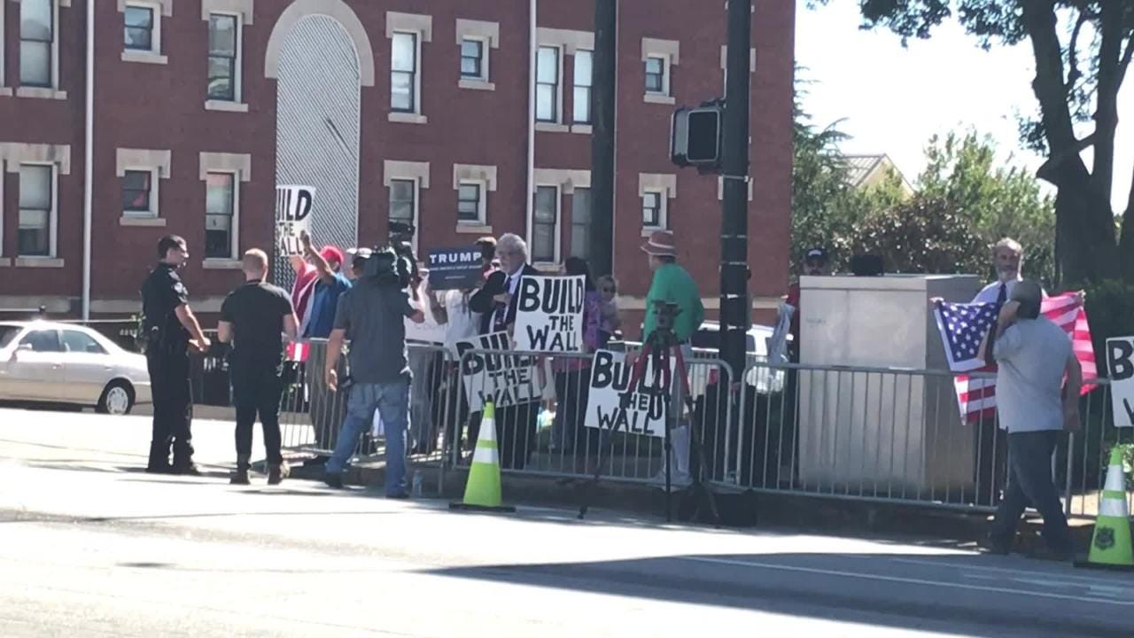 """Protestors holding """"Build the Wall"""" signs gathered on Washington Street in Downtown Greenville on Saturday, October 13."""