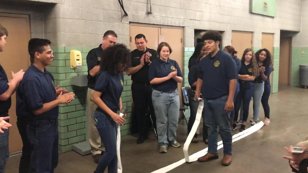Abilene ISD students enrolled in the 2018-19 fire academy separated a hose instead of cutting a ribbon to mark the opening of the new facility