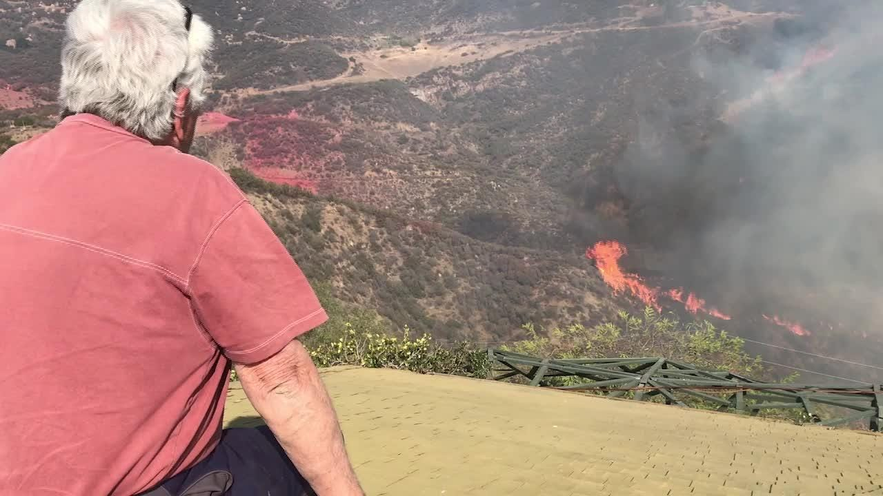 Rick Mecagni watches as an airplane drops retardant around his house in the Santa Monica Mountains on Nov. 10, 2018, as the Woolsey Fire continued to burn.