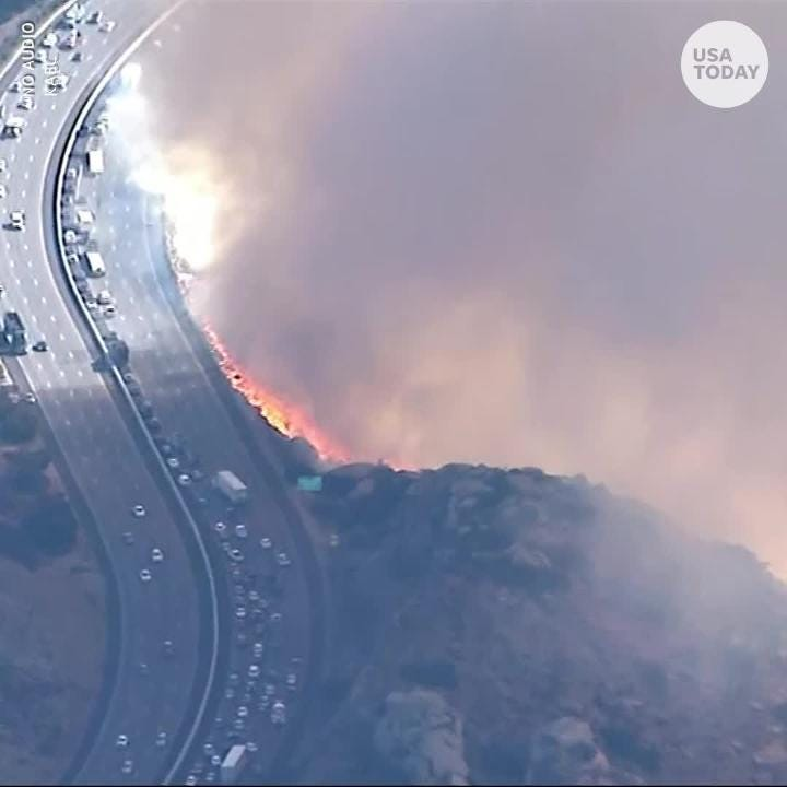 VIDEO: Fire crews douse flames right next to drivers along the 118 Freeway in Simi Valley, California.