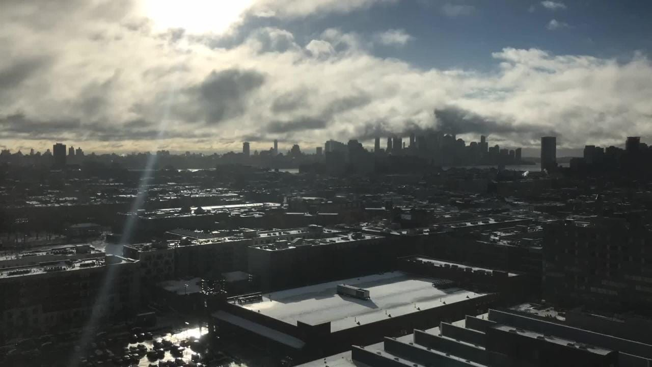 The snow storm that caused a commuting nightmare on Thursday night finally breaks up on Friday morning. View is of Hoboken, Jersey City and lower NYC.