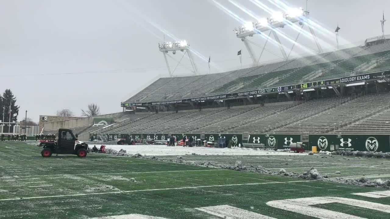 Crews clear snow from Sonny Lubick Field at Canvas Stadium before the CSU football team plays Utah State.
