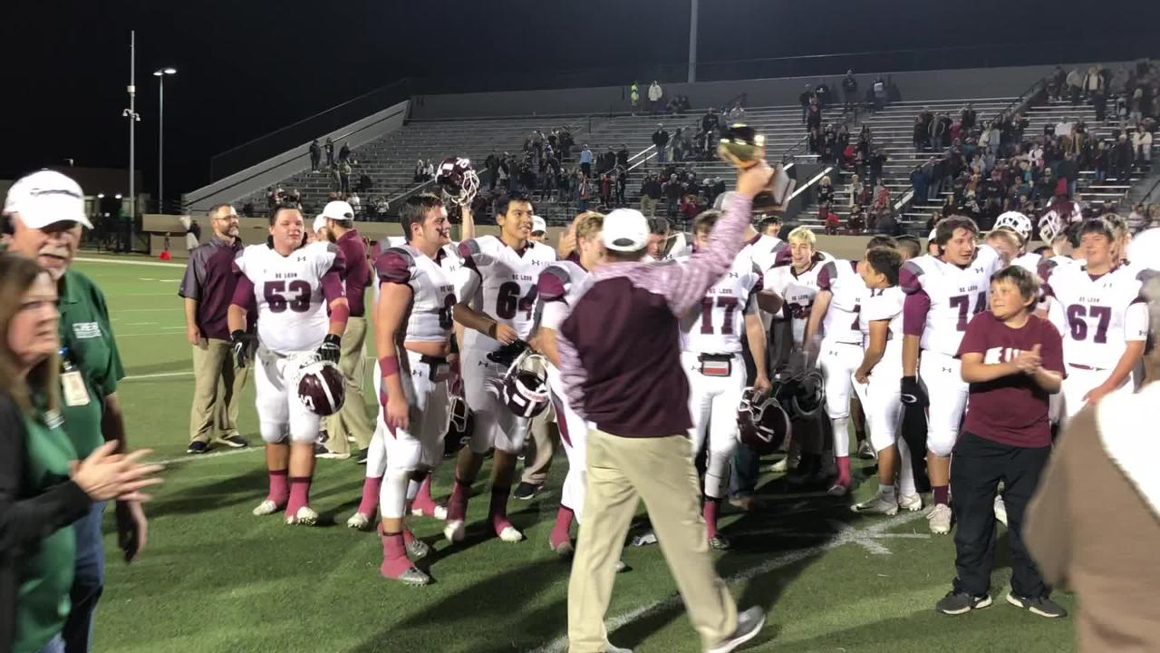 De Leon head coach David Yeager accepts the Region II-2A Division I area trophy following Friday's 31-20 win against Wolfe City at Pennington Field.