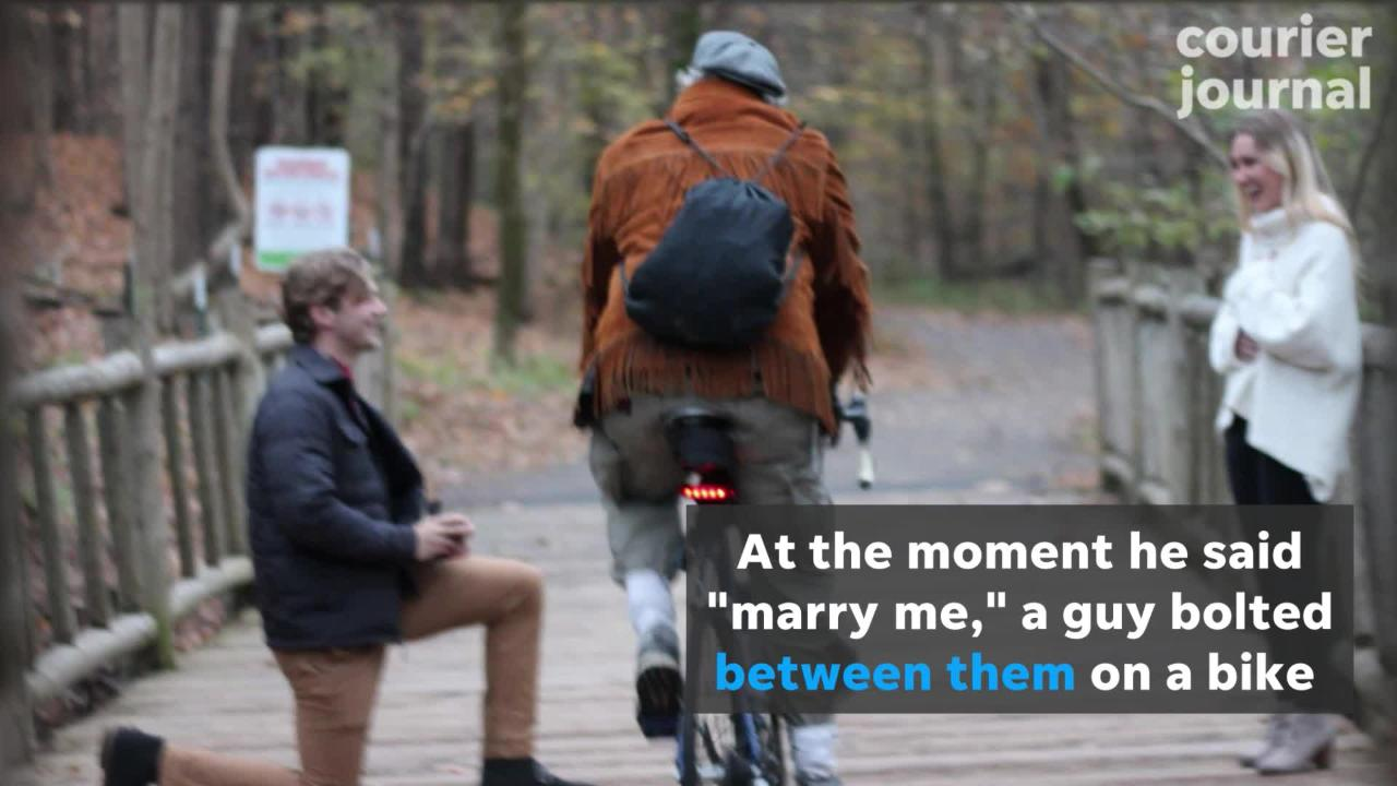 A Louisville couple is searching for a man on a bike who rode between them at the exact moment of their engagement.