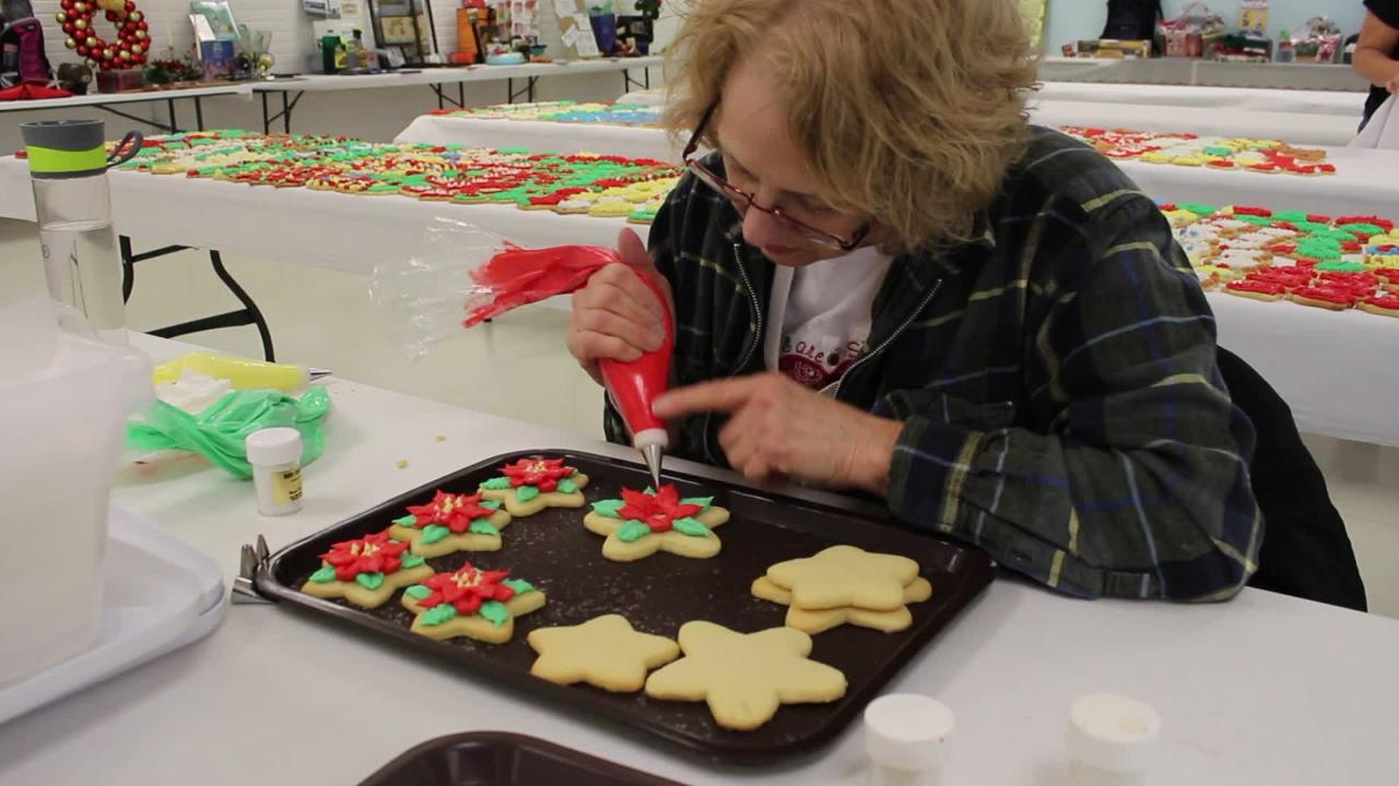 Debbie Miller decorates cookies with poinsettias for the PAWS Cookie Walk on Dec. 8.