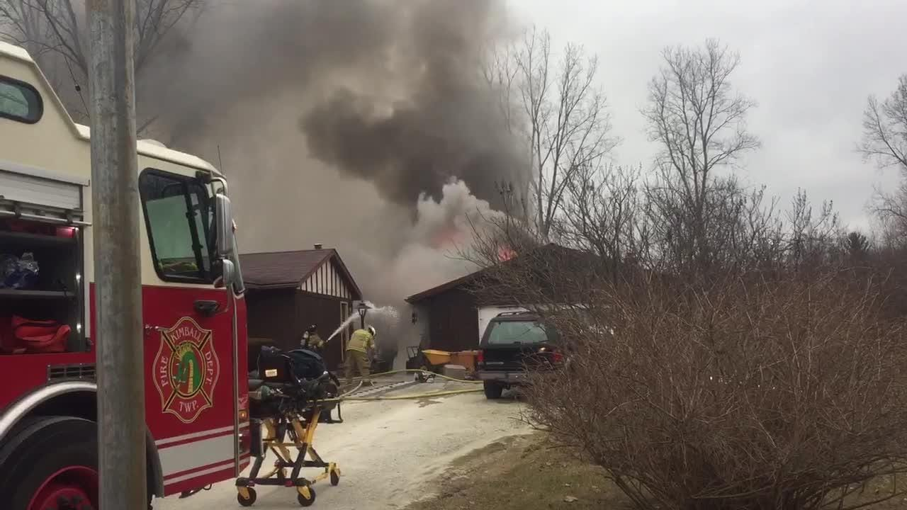 Dense smoke pours from a burning garage as firefighters work to control a fire in its attic.