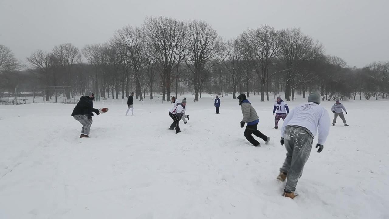A group of friends didn't let the accumulating snow and frigid temperatures dissuade their football game in Cobbs Hill Park.