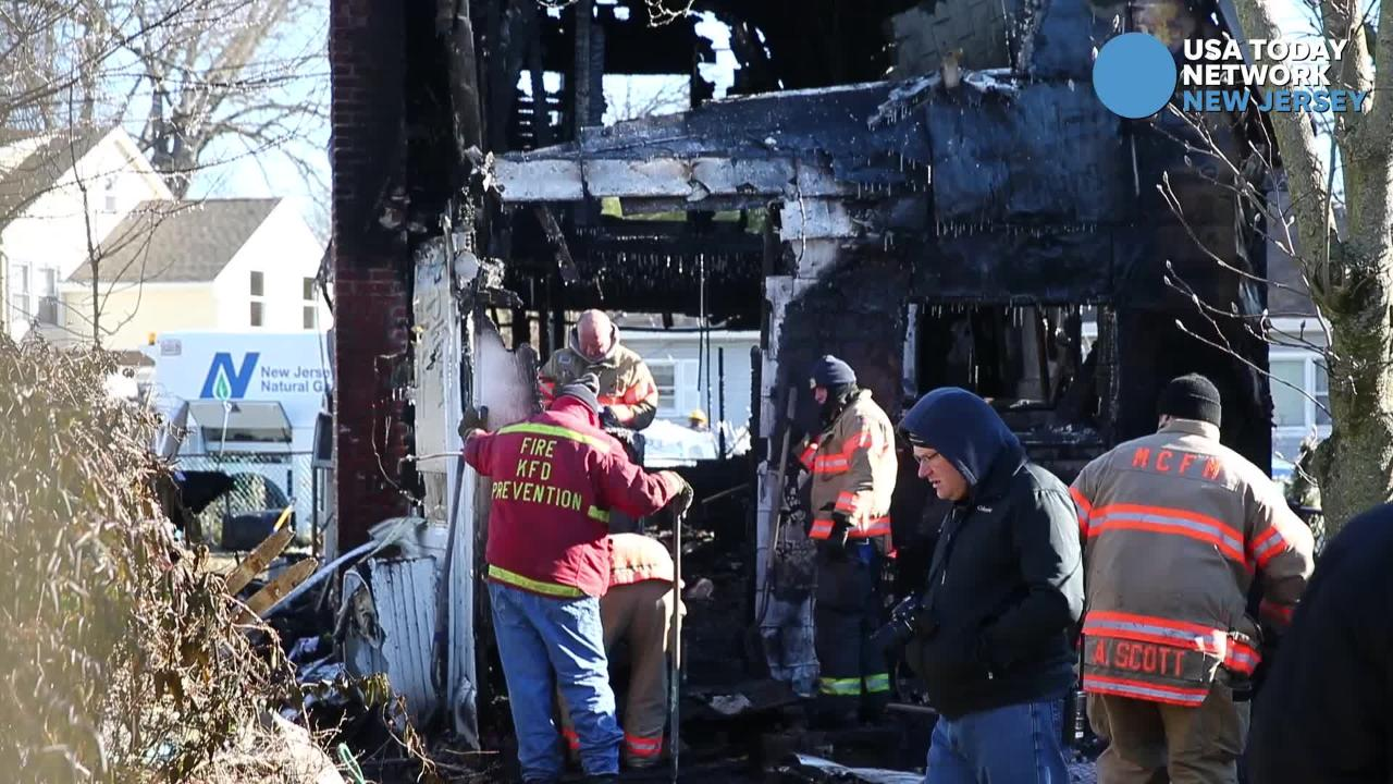 Investigators examine the scene of a fire on Cottage Place in Keansburg that destroyed the home and damaged another adjacent one.